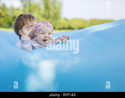 Siblings playing on inflatable sofa outdoors. Baby girl and older brother having fun together in park. - Stock Photo