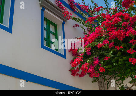 Colorful view with red flowers and a white Canarian house in the town Puerto de Mogan , Gran Canaria, Canary Islands, Spain. - Stock Photo