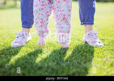 Cropped view of mother supporting baby daughter and helping her make first steps. Closeup of mom and daughter's feet on green grass in summer park. - Stock Photo