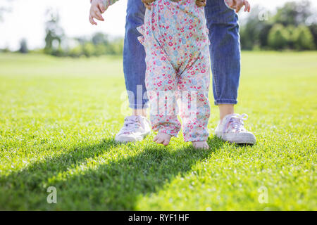 Cropped view of mother supporting baby daughter and helping her make first steps. Mom and daughter's feet on green grass in summer park. - Stock Photo