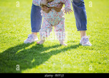 Cropped view of mother supporting baby daughter and helping her make first steps. Mom and daughter walking on green grass in summer park. - Stock Photo