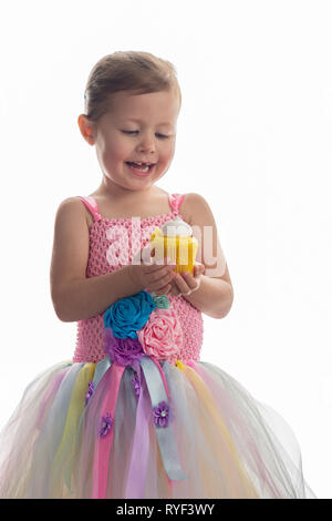 Little girl in pretty pink tutu dress with fabric flowers holding lemon cupcake with meringue on white, selective focus - Stock Photo