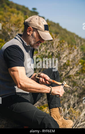 Man sitting on a rock in the nature with great view carving a stock of a tree with a knife - Stock Photo
