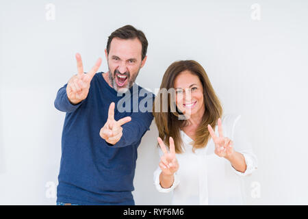Beautiful middle age couple in love over isolated background smiling looking to the camera showing fingers doing victory sign. Number two. - Stock Photo