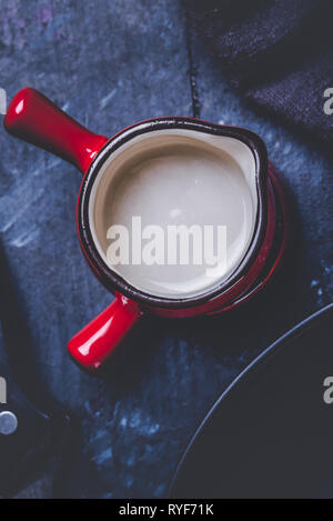 Vertical photo with top view on two cups. Cups or small bowls have saturated red color, black edge and white inner side. Cups are stacked and placed o - Stock Photo