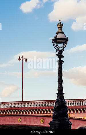 Vintage street light poles against blue sky and white clouds - Stock Photo