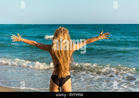 Concept of woman spreading hands embracing freedom new life happiness life goals success - Rear view of girl on beach wide open raised arms - Happy yo - Stock Photo