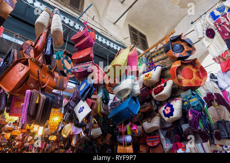 View of a store with a variety of leather bags, accessories and traditional clothing in the medina market in  Tunis, Tunisia - Stock Photo