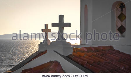 Late afternoon with the sun sinking above the mountains of the Mani peninsula and the church of Agia Paraskevi in the foreground on the Peloponnese in - Stock Photo
