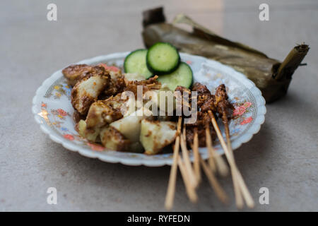 Chicken satay with rice cake (lontong), a street food that you can find everywhere in Indonesian street. - Stock Photo
