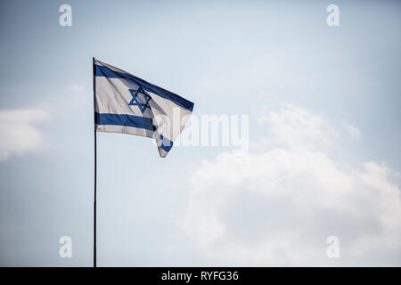 Israel Flag on blue background in the wind. real photo. - Stock Photo