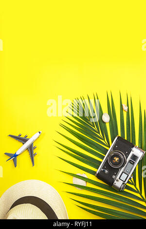 Top view traveler accessories tropical palm leaf, white straw hat, airplane toy, retro camera and seashells on yellow colorful background with space f - Stock Photo