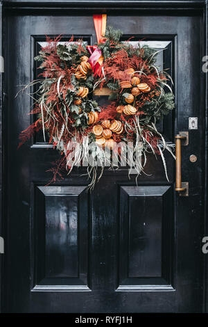 Close up of a black front door with an autumnal wreath decoration on a facade of traditional English house in London, UK. - Stock Photo