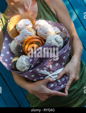 Girl holds in her hands an original bouquet made of delicious buns on a blue background - Stock Photo