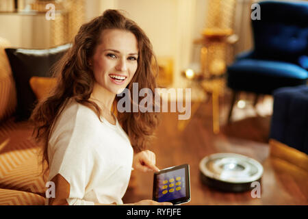 Portrait of smiling fit woman with long brunette hair in the modern house using smart home application on tablet PC and robot vacuum cleaning floor in - Stock Photo