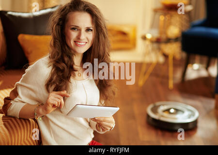 Portrait of smiling young woman with long brunette hair in the modern house using smart home application on tablet PC and robot vacuum cleaning floor  - Stock Photo