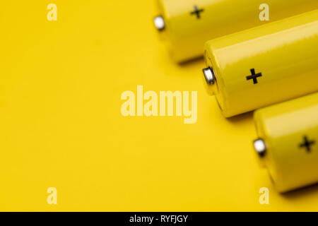 Close up shot of yellow AAA alkaline or rechargeable NiMH batteries or on yellow background, shallow focus - Stock Photo
