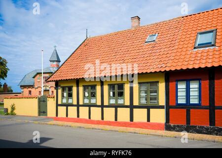 ALLINGE, DENMARK - AUGUST 24, 2018: Traditional colorful half timbered houses, historic old red brick technical school building in the background - Stock Photo