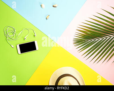 Top view traveler accessories layout: tropical palm leaf, white straw hat, mobile phone and headphones, seashells on colorful background. Travel vacation summer concept. flat lay composition. - Stock Photo