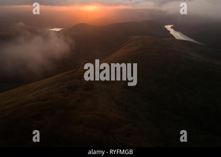 Aerial image looking across low cloud towards the setting sun from above Carlavin Hill near Talla Reservoir in the Tweed Valley. - Stock Photo