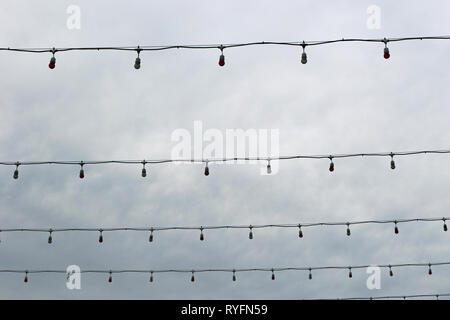Unlit strings of lights strung across a street on a dreary day. - Stock Photo