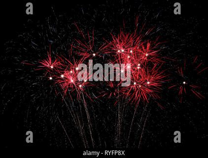 Red fireworks with white highlights light the sky on July 4th, 2015 - Stock Photo