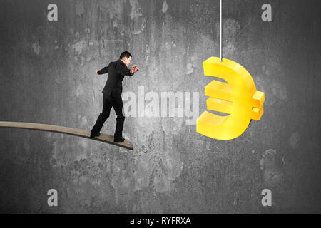 Businessman balancing on wooden board with golden euro symbol and concrete wall background - Stock Photo