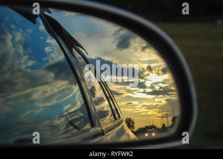 Beautiful sunset is reflected in the rearview mirror of a car traveling - Stock Photo