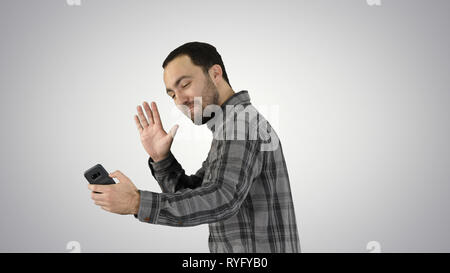 Young man taking selfie picture with smart-phone on gradient background. - Stock Photo