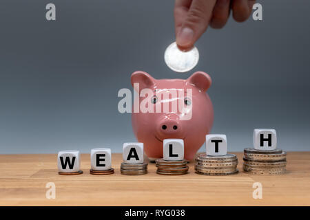 Symbol for increasing wealth. Dice placed on stacks of coins form the word 'WEALTH'. In the background a coin is put into a piggy bank. - Stock Photo