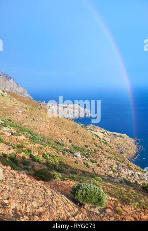 Wild hilly coastline of Creta island after a rain with a rainbow - Stock Photo