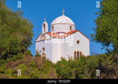 White-washed traditional Christian Orthodox church in Crete island, Greece, among greenery - Stock Photo