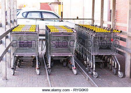 Poznan, Poland - February 24, 2019: Three rows of metal locked shopping carts of a German Netto supermarket. - Stock Photo