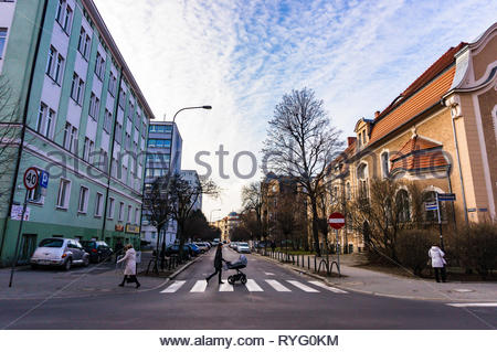 Poznan, Poland - March 1, 2019: Street with woman with baby buggy walking on a zebra crossing in the city center. - Stock Photo