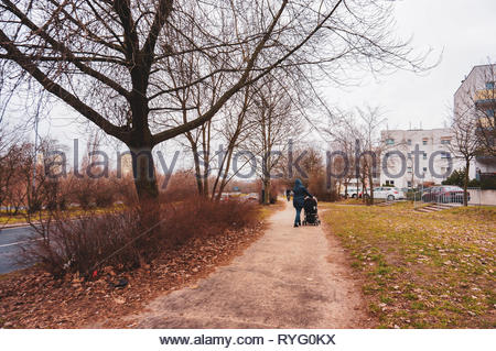 Poznan, Poland - March 3, 2019: Small footpath along a road and green grass with walking people on the Inflancka street. - Stock Photo