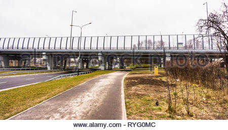 Poznan, Poland - March 3, 2019: Footpath with walking people in the distance leading to a bridge on the Inflancka street. - Stock Photo