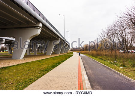 Poznan, Poland - March 3, 2019: Bicycle route and pathway with red line next to a bridge in a park. - Stock Photo