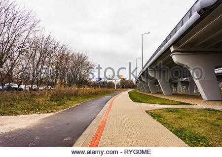 Poznan, Poland - March 3, 2019: Footpath and bike route next to a bridge on a cloudy day. - Stock Photo