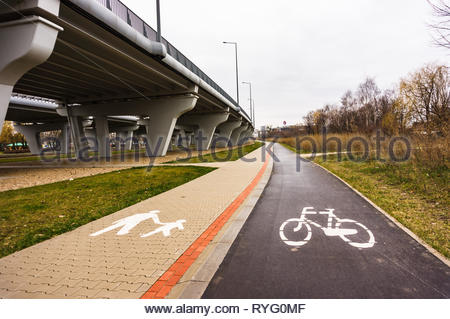 Poznan, Poland - March 3, 2019: Bike route and footpath with symbols along a bridge at a park. - Stock Photo