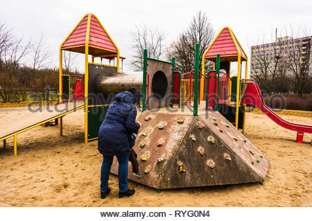 Poznan, Poland - March 3, 2019: Woman helping toddler boy on a wooden climb wall at a playground. - Stock Photo