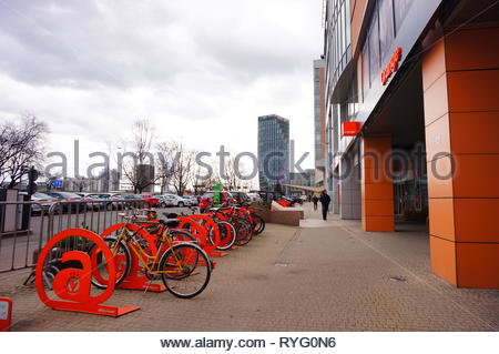 Poznan, Poland - March 8, 2019: Bicycles locked on racks in front of a Orange shop in the Globis office building on the Roosevelta street. - Stock Photo