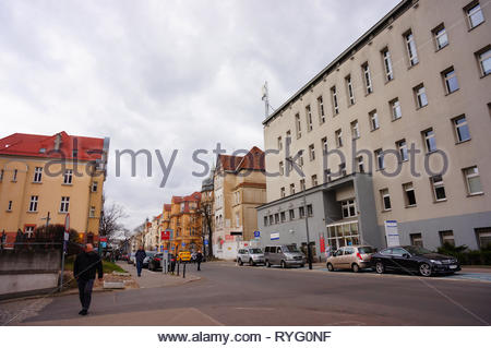 Poznan, Poland - March 8, 2019: People and parked cars on the Slowackiego street in the city center. - Stock Photo
