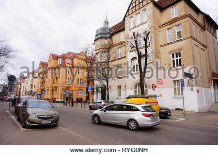 Poznan, Poland - March 8, 2019: Parked cars and driving on a road by a hostel and small shop on the Slowackiego street. - Stock Photo