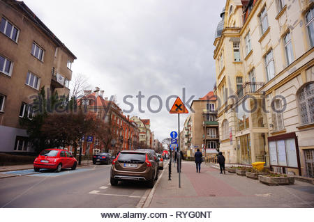 Poznan, Poland - March 8, 2019: Parked cars and people walking on a sidewalk with apartment building on the Slowackiego street. - Stock Photo