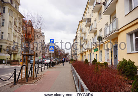 Poznan, Poland - March 8, 2019: Shrub and barrier along apartment building and road on the Slowackiego street. - Stock Photo