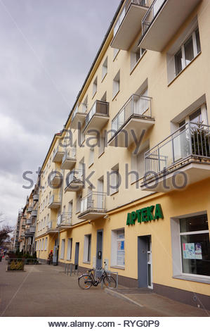 Poznan, Poland - March 8, 2019: Pharmacy shop in a apartment building with balconies. Bicycle parked by the entrance on a sidewalk. Located in the Slo - Stock Photo