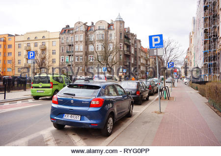 Poznan, Poland - March 8, 2019: Parked blue Suzuki Baleno car false parking by a sidewalk on the Slowackiego street in the city center. - Stock Photo