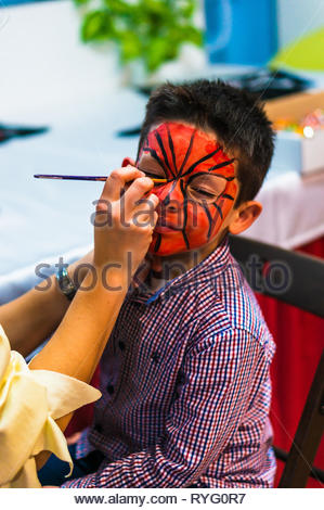 Poznan, Poland - March 3, 2019: Young boy with red and black paint on his face being painted with a brush by a woman during a birthday celebration par - Stock Photo