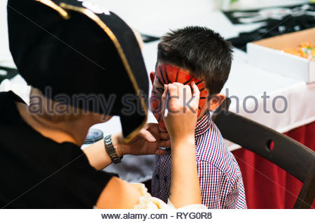 Poznan, Poland - March 3, 2019: Woman in pirate costume painting face of a boy during a birthday celebration party. - Stock Photo