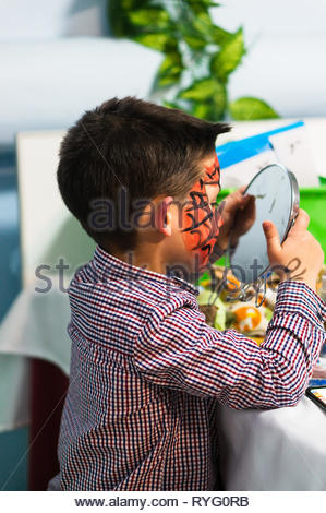 Poznan, Poland - March 2, 2019: Young boy with red face paint looking in a mirror by a table during a birthday celebration party. - Stock Photo